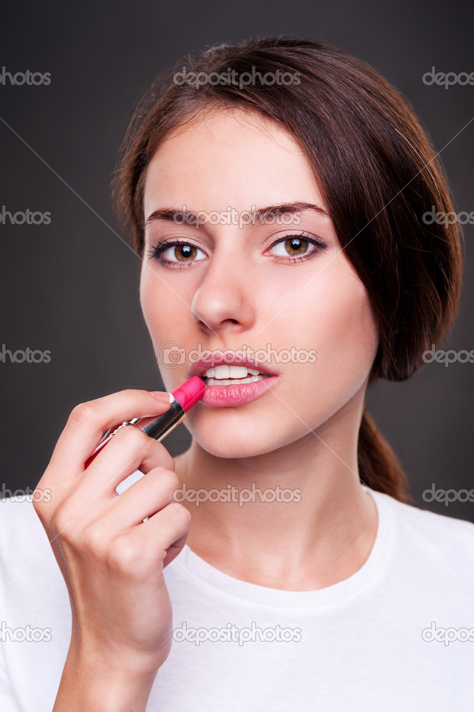 Young attractive woman painting her lips and looking at camera  — Stock Photo #12553016