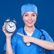 Smiley nurse pointing at alarm clock — Stock Photo #13133870