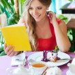 Woman sitting in cafe and reading book — Stock Photo