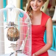 Woman standing near white cage with birds - Stock Photo
