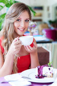 Woman drinking tea and smiling — Stock Photo