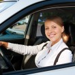 Woman driving the car and smiling — Stok fotoğraf