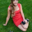 Woman in red dress sitting on green grass — Stock Photo