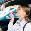 Woman sitting in the car and painting her lips — Stock Photo
