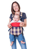 Mother holding her baby in the knapsack — Stock Photo