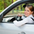 Young woman driving the car and smiling — Stock Photo