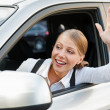 Stock Photo: Woman sitting in the car and waving her hand