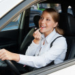 Woman driving the car and painting her lips - Foto de Stock