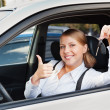Womholding car key and showing thumbs up — Stock Photo #13771962