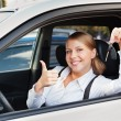 Woman holding car key and showing thumbs up — Stock Photo