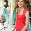 Pretty woman near white cage — Stock Photo