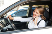 Woman sitting in the car and talking on the phone — Stock Photo