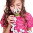 Cute girl smelling spring flowers  — Stock Photo
