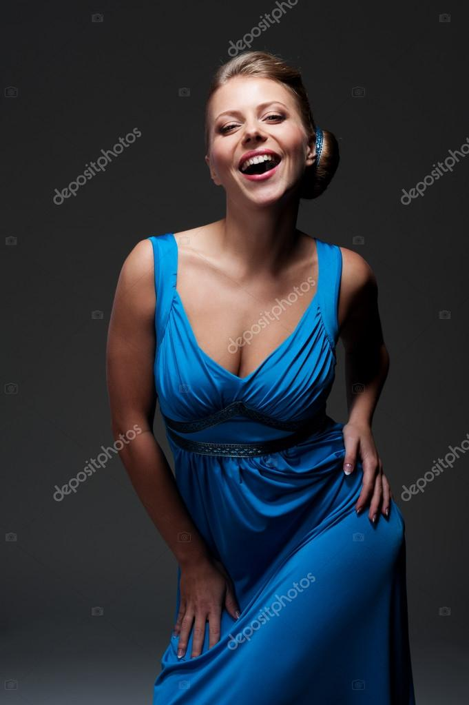 Attractive woman looking at camera and laughing over dark background  Stock Photo #14030167