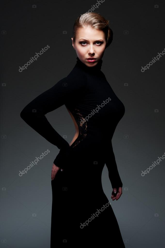 Graceful young woman in black dress against dark background — Stock Photo #14030422