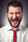 Screaming man over grey background — Stock Photo