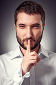 Serious man showing silent sign — Stock Photo