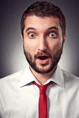 Surprised man over grey background — Stock Photo
