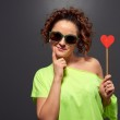 Funny girl in sunglasses holding small heart — Stock Photo #19717533