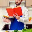 Stock Photo: Handsome young mreading cookbook attentively