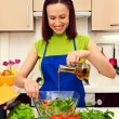 Housewife adding oil in salad - Stock Photo