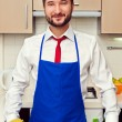 Man in blue apron in the kitchen — Stock Photo #21672013