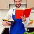 Man in apron reading the cookery book — Stock Photo