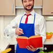 Smiley young man pointing at the cookbook — Stock Photo #21672043