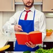 Young man pointing at the cookbook - Stock Photo