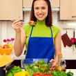 Woman with spoon of salad standing in the kitchen — Stock Photo