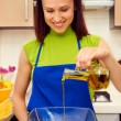 Young smiley housewife preparing vegetable salad — Stock Photo