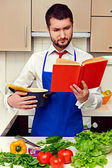 Concentrated young man reading cookbook — Stock Photo