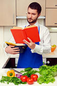 Handsome young man reading cookbook attentively — Stock Photo
