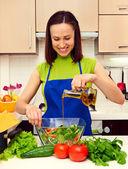 Huisvrouw olie in salade toe te voegen — Stockfoto
