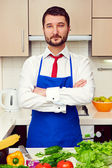 Man in formal wear and blue apron — Stock Photo