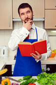 Young cook with cookbook thinking about recipe — Stock Photo