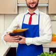 Handsome man in blue apron holding pan — Stock Photo