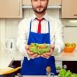 Healthy man in blue apron holding salad — Stock Photo #22065667
