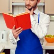 Man in blue apron reading cookbook — Stock Photo #22065703