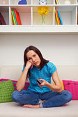Bored woman watching tv — Stock Photo