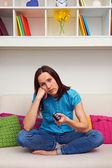 Bored woman watching tv — Stock Photo
