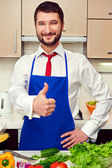 Smiley man in blue apron showing thumbs up — Stock Photo