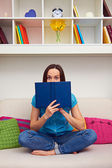 Woman looking out from behind of the book — Stock Photo