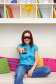 Woman sitting on the sofa and watching 3d film — Stock Photo