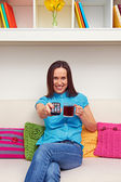 Woman holding cup of tea and remote controller — Stock Photo