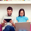 Couple sitting on sofa and holding computers — Stock Photo #22169919