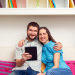 Stock Photo: Couple sitting on sofa and holding the tablet pc