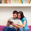 Couple sitting on sofa and looking at the tablet pc — Stock Photo #22169931