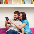 Smiley couple sitting on sofa — Stock Photo #22169989
