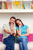 Bored couple watching TV — Stock Photo
